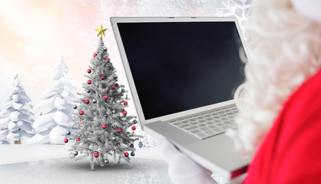 Father christmas using his laptop against christmas tree in snowy landscape