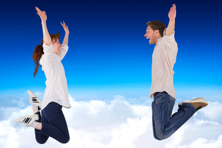 middleaged: Couple jumping in the air against blue sky over clouds Stock Photo