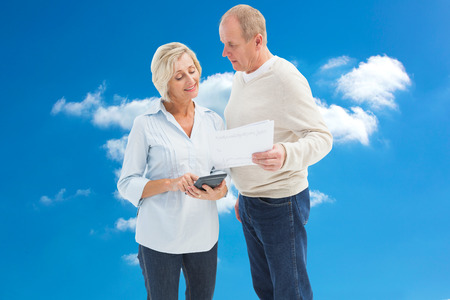 credit crunch: Mature couple working out their bills against cloudy sky