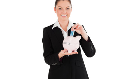 inserting: Charming woman in suit inserting a money bill in a pink piggy bank against 2015 in grey