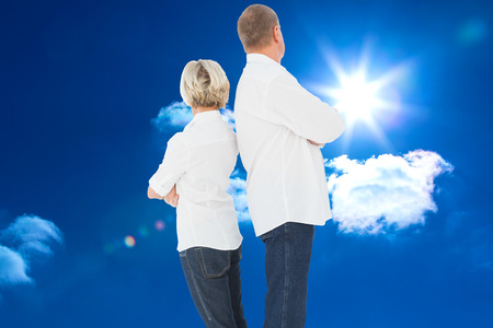not talking: Upset couple not talking to each other after fight against bright blue sky with clouds