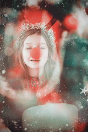 nariz roja: Festive little girl wearing red nose against candle burning against festive background Foto de archivo