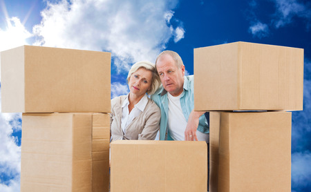 mature adult women: Stressed older couple with moving boxes against bright blue sky with clouds