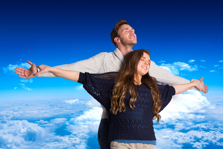 arms out: Romantic young couple with arms out against mountain peak through clouds