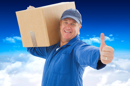 boiler suit: Happy delivery man holding cardboard box against bright blue sky over clouds