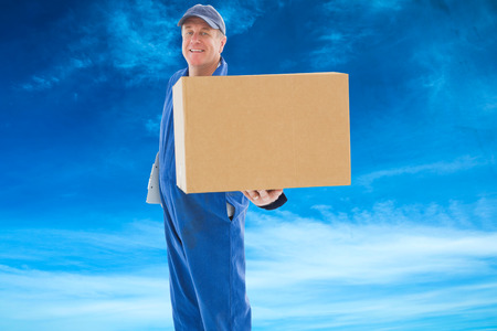 boiler suit: Happy delivery man showing cardboard box against blue sky Stock Photo