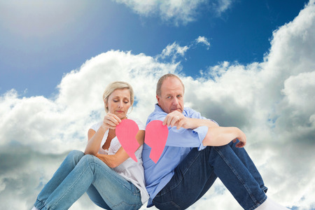 strife: Sad mature couple holding a broken heart against blue sky with clouds Stock Photo