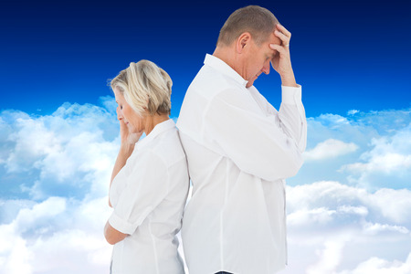 not talking: Upset couple not talking to each other after fight against bright blue sky over clouds