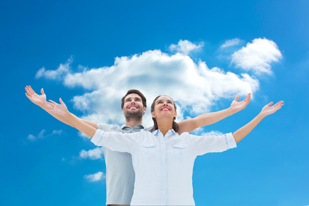 woman looking up: Cute couple standing with arms out against cloudy sky