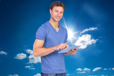 scrolling: Man scrolling through tablet pc against cloudy sky with sunshine