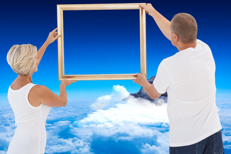 hanging up: Mature couple hanging up picture frame against mountain peak through the clouds Stock Photo