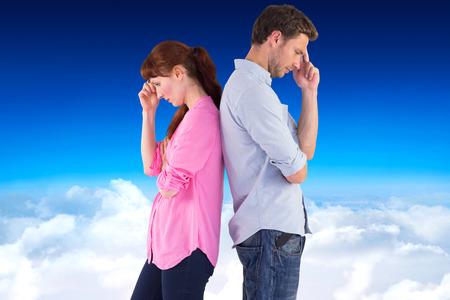 irritated: Irritated couple ignoring each other against blue sky over clouds