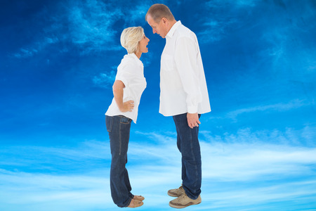 pareja discutiendo: Angry pareja mayor discutiendo entre sí contra el cielo azul Foto de archivo
