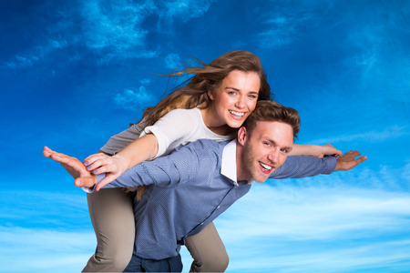 man carrying woman: Smiling young man carrying woman against blue sky