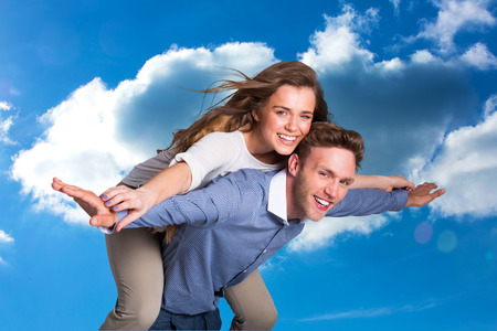 man carrying woman: Smiling young man carrying woman against cloudy sky