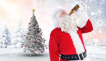 santa outfit: Father christmas drinking a beer against christmas tree in snowy landscape