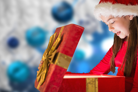 opening gift: Little girl opening gift against christmas decorations hanging from branch Stock Photo