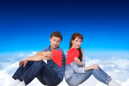 snapped: Couple holding a broken heart against blue sky over clouds