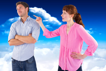 fighting styles: Woman arguing with uncaring man against bright blue sky with clouds