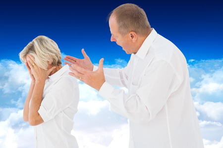 cowering: Angry man shouting at his partner against bright blue sky over clouds