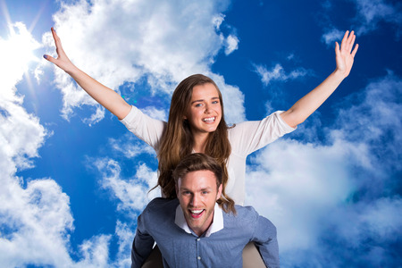 man carrying woman: Smiling young man carrying woman against bright blue sky with clouds
