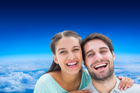 altitude: Cute couple smiling at camera against blue sky over clouds at high altitude