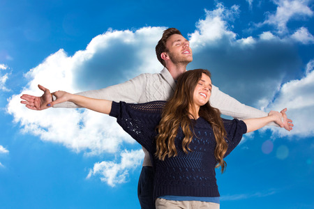 arms out: Romantic young couple with arms out against cloudy sky