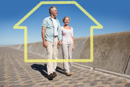 chinos: Happy senior couple walking on the pier against house outline Stock Photo
