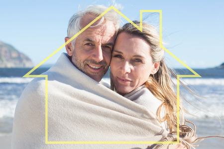 hair wrapped up: Smiling couple wrapped up in blanket on the beach against house outline