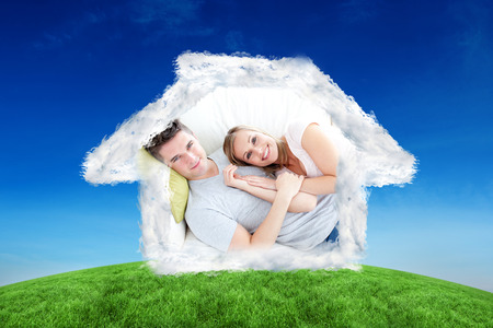 caress: Caress young couple lying together on the sofa in the livingroom against green hill under blue sky