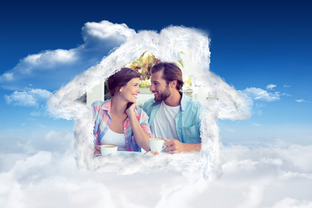 customer facing: Happy couple enjoying coffee together against bright blue sky with clouds Stock Photo