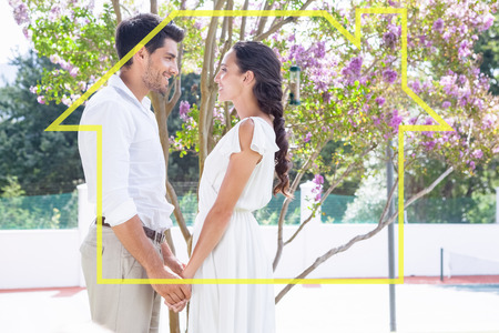 house outline: Attractive couple standing in garden holding hands against house outline
