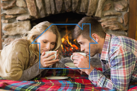 couple lit: Romantic couple drinking tea in front of lit fireplace against house outline