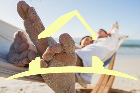 sandy feet: Close up of sandy feet of couple in a hammock against house outline Stock Photo