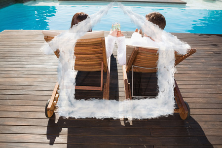 flute structure: Couple toasting champagne by swimming pool against house outline in clouds Stock Photo