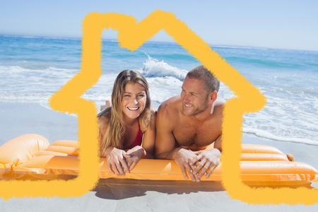 lilo: Cheerful cute couple in swimsuit lying on the beach against house outline