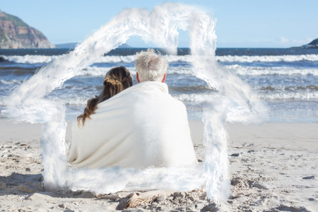 hair wrapped up: Couple sitting on the beach under blanket looking out to sea against house outline in clouds