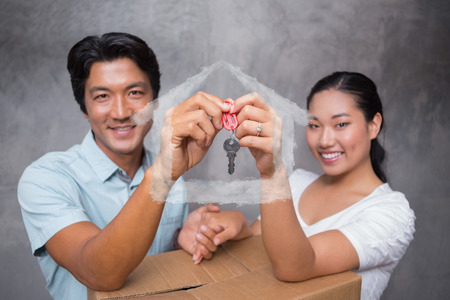 key box: Happy couple holding house key and leaning on moving box against house outline in clouds