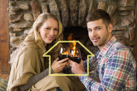 couple lit: Romantic couple toasting wineglasses in front of lit fireplace against house outline Stock Photo