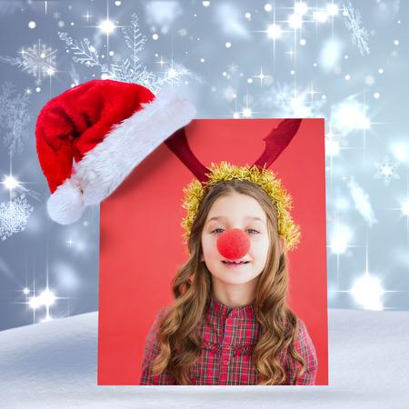 nariz roja: Ni�a festiva que desgasta la nariz roja contra el copo de nieve dise�o brillante en azul