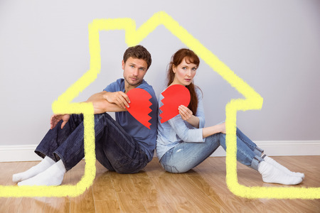 snapped: Couple holding a broken heart against house outline Stock Photo