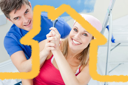 Hugging couple having fun while painting a room against house outline