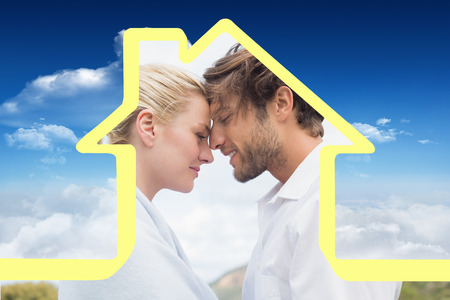 hair wrapped up: Cute smiling couple standing outside facing each other against bright blue sky with clouds Stock Photo