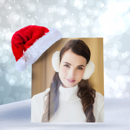 ear muffs: Pretty brunette with ear muffs smiling at camera against light glowing dots design pattern