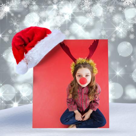 red nose: Festive little girl wearing red nose against shimmering light design on grey