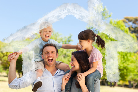 house outline: House outline in clouds against parents giving  children a piggyback Stock Photo