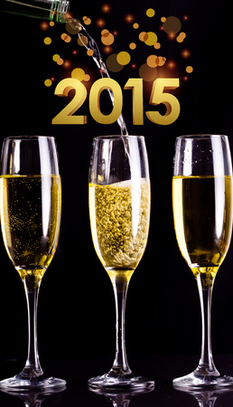 full filled: golden 2015 against two full glasses of champagne and one being filled Stock Photo