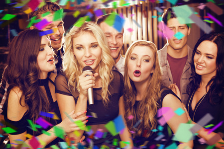 karaoke: Happy friends singing karaoke together against flying colours Stock Photo