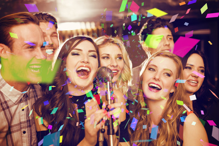 Happy friends singing karaoke together against flying colours Standard-Bild