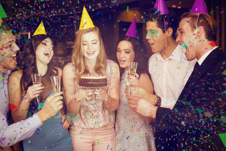 celebrating female: Attractive friends celebrating a birthday against flying colours
